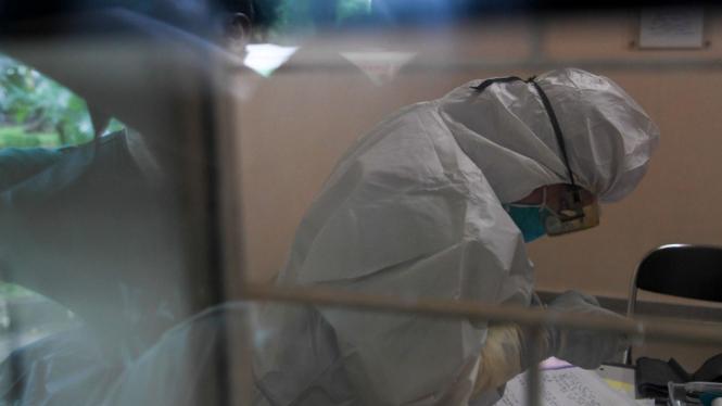 Petugas medis menggunakan alat pelindung diri (APD).