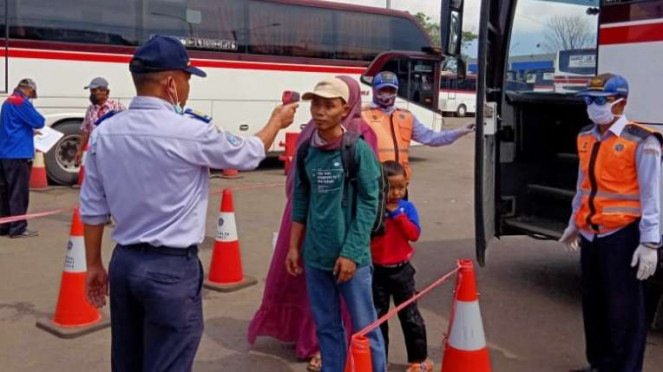 Petugas memeriksa suhu tubuh sejumlah perantau berprofesi pemangkas rambut asal Garut yang mudik ke kampung halaman menyusul wabah corona.