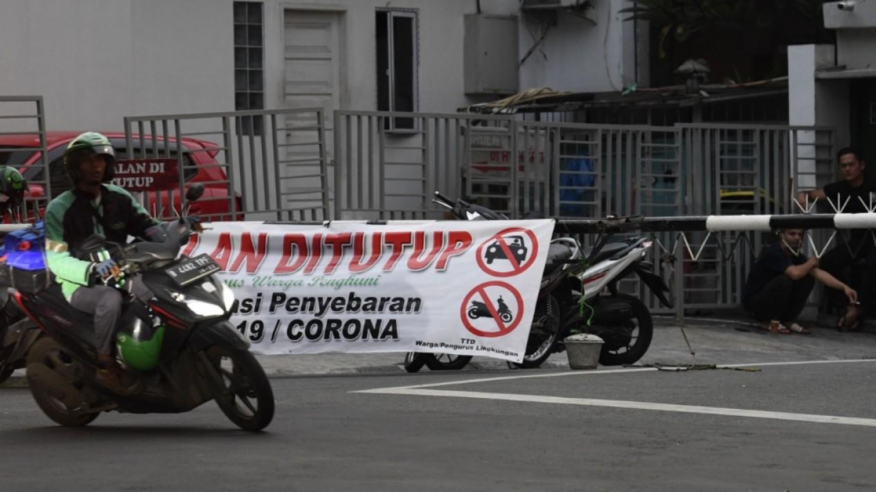 Pengendara sepeda bermotor melintasi spanduk penutupan jalan di kawasan Pondok Pinang, Jakarta, Rabu 1 Maret 2020.