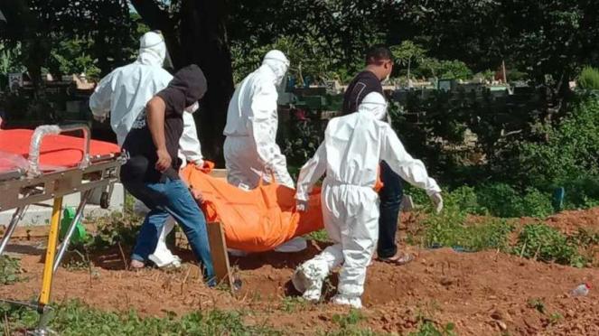 Petugas medis memakamkan jenazah diduga terkena corona.
