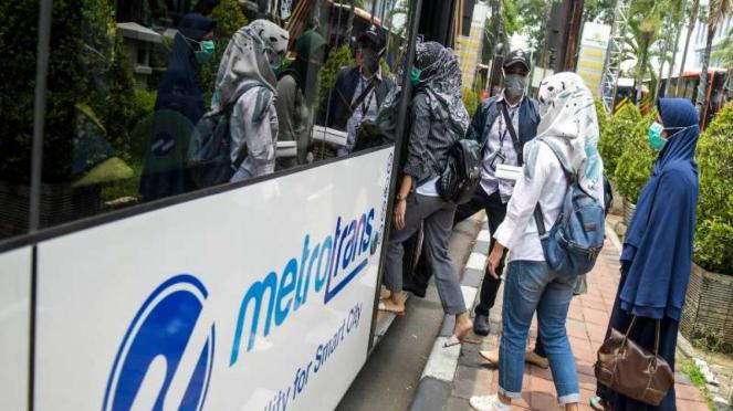 Penumpang bus TransJakarta mengenakan masker