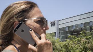 Seseorang sedang menelepon pakai iPhone depan kantor NSO Group di Israel.