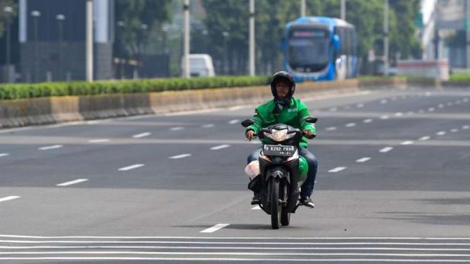 Driver ojek online (Ojol) melintasi Jalan MH Thamrin, Jakarta Pusat.