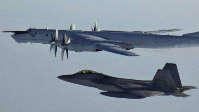 VIVA Militer: Jet Siluman AS F-22 (bawah) mengawal pesawat intai Rusia Tu-142