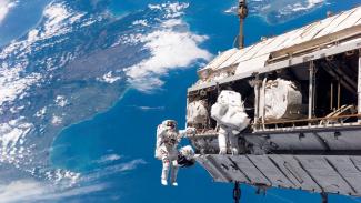 Astronot bekerja di luar Stasiun Luar Angkasa Internasional (ISS).