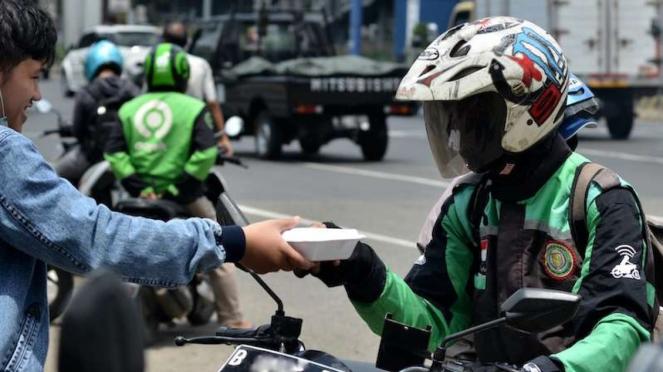 Seorang relawan saat membagikan paket makan siang gratis kepada pengemudi ojek online (ojol) beberapa waktu lalu.