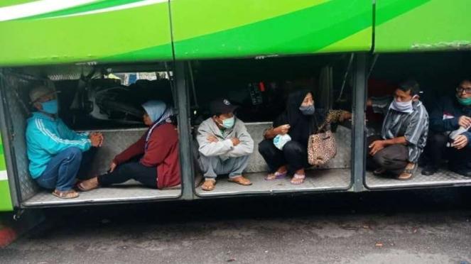 Penumpang rela duduk di bagasi bus demi bisa mudik