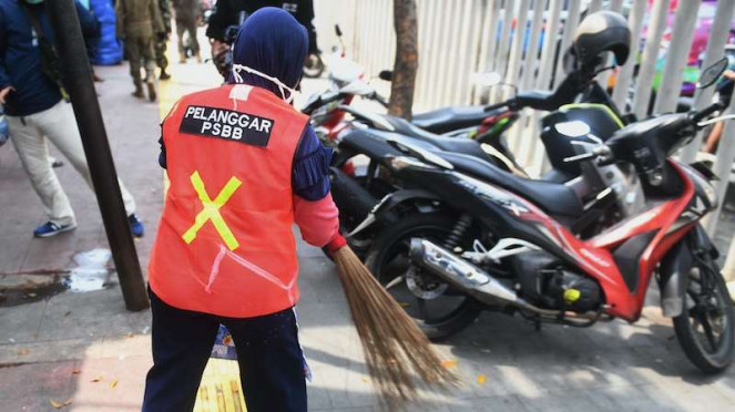 Seorang warga yang terjaring razia penindakan pelanggaran aturan Pembatasan Sosial Berskala Besar (PSBB) oleh Satpol PP menjalani hukuman dengan cara membersihkan sampah di Tanah Abang, Jakarta, Rabu (13/5/2020).