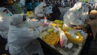 Petugas melakukan pemeriksaan cepat (Rapid Test) Corona di Pasar Kembang, Suraba