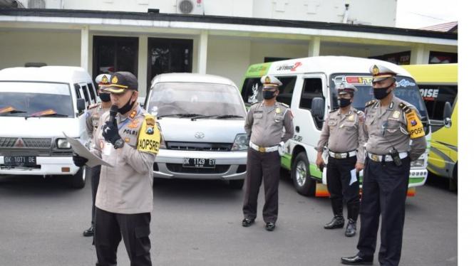 Polisi saat mengamankan mobil travel yang membawa pemudik dari madura