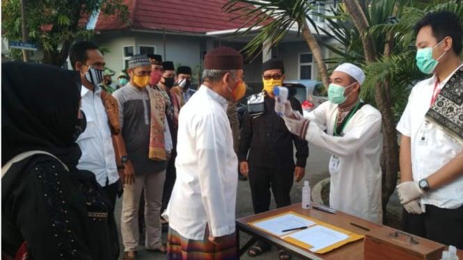 Jemaah melakukan pengukuran suhu tubuh sebelum masuk masjid di tengah pandemi COVID-19