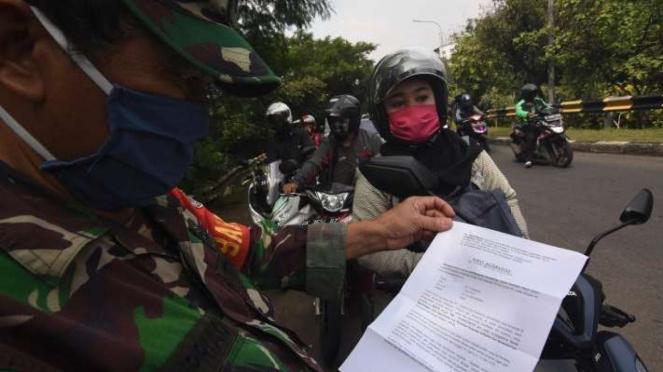 Petugas memeriksa Surat Izin Keluar Masuk (SIKM) Jakarta terhadap pengendara kendaraan bermotor yang melintas menuju Jakarta di perbatasan wilayah, Depok, Jawa Barat, Rabu (27/5/2020).