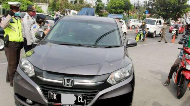 Petugas kepolisian dan Dishub Jakarta memeriksa surat kelengkapan
