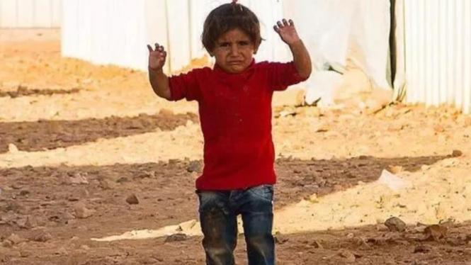 Seorang gadis kecil dari kamp pengungsi Yordania saat puncak Perang Sipil Suriah. Anak itu mengira bahwa kamera adalah senapan sehingga ia langsung mengangkat tangan sebagai tanda untuk menyerah. Foto diambil oleh Rene Schulthoff.