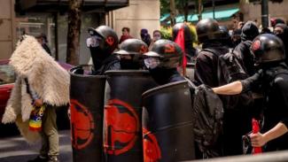 Pengunjung rasa dengan simbol Antifa di perisai mereka.