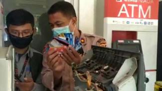 Polisi memeriksa satu mesin ATM yang sempat dijadikan objek untuk menipu di SPBU Jalan Narogong, Kecamatan Cileungsi, Kabupaten Bogor, Jawa Barat.