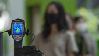 Karyawan mal antre untuk mencoba alat pendeteksi suhu tubuh saat new normal.