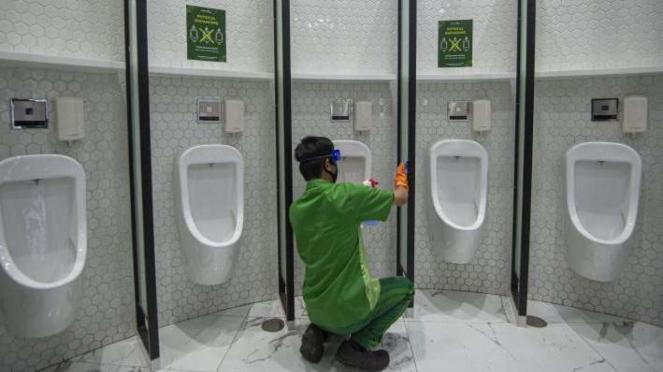 Petugas membersihkan fasilitas toilet dengan berstiker tanda jaga jarak di Mal