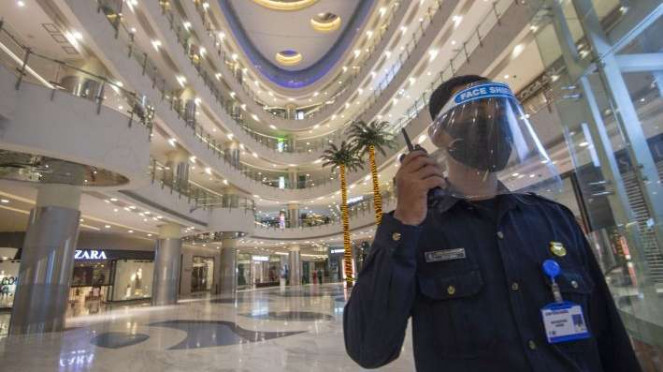Petugas keamanan mengenakan masker dan berpelindung wajah saat bertugas di Mal