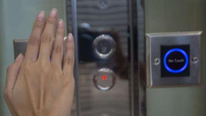 Karyawan mencoba tombol lift dengan sensor tanpa sentuh di Mal