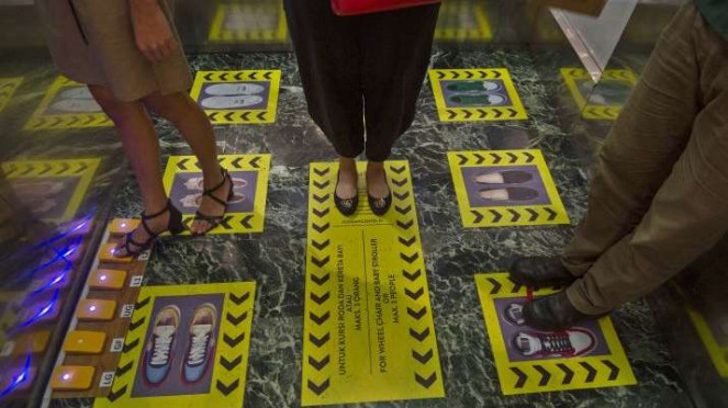 Karyawan mencoba fasilitas tombol lift dengan kaki di Mal Central Park Jakarta