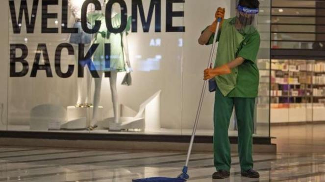 Petugas bermasker dan berpelindung wajah membersihkan lantai di Mal