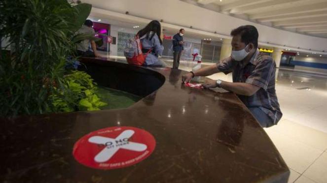 Petugas memasang stiker tanda jaga jarak di Mal Central Park Jakarta