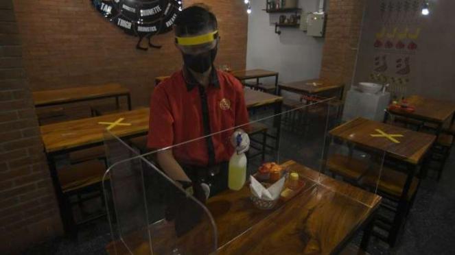 Karyawan membersihkan mika pembatas meja makan di Restoran Bebek Kaleyo Jakarta