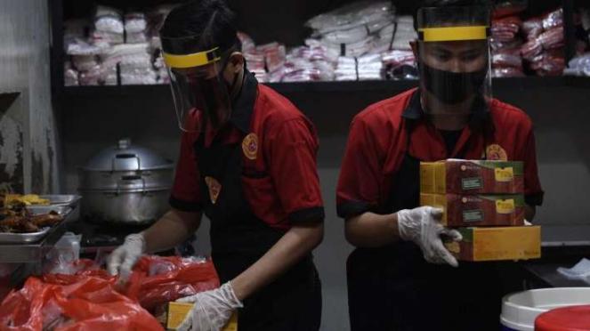 Karyawan mengenakan face shield saat mempersiapkan pesanan makanan di restoran