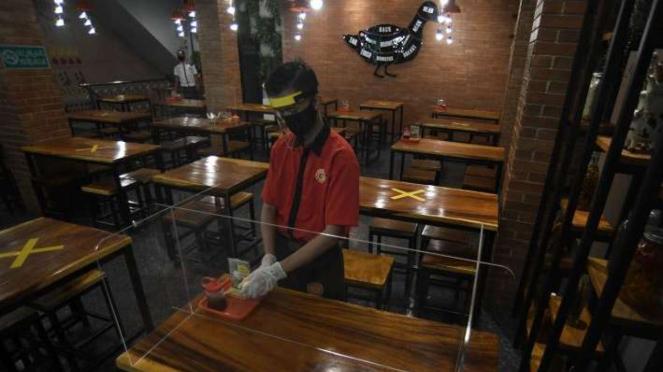 Karyawan membersihkan meja makan yang dipasangi mika pembatas di Restoran