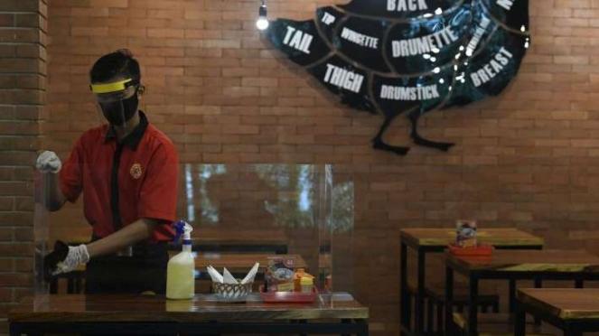Karyawan membersihkan mika pembatas meja makan di restoran