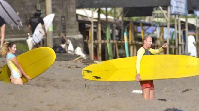Wisatawan membawa papan selancar di kawasan Pantai Canggu, Badung, Bali