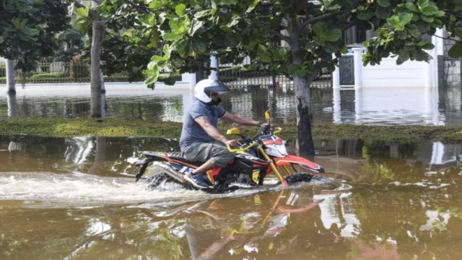 Pengendara motor melintas saat banjir rob menggenangi Kompleks Pantai Mutiara