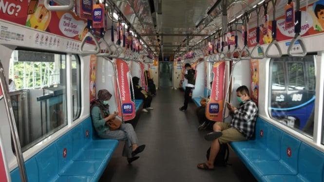 Penumpang duduk dengan menjaga jarak di dalam kereta MRT