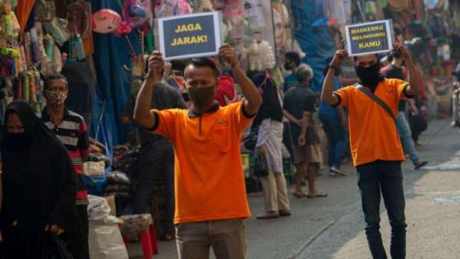 Petugas pengelola pasar berkampanye pencegahan COVID-19 dengan membawa poster berisi pesan di Pasar Jatinegara, Jakarta, Kamis (11/6/2020).
