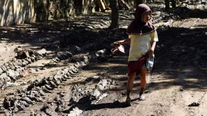 Seorang anak berjalan diantara sisa-sisa lumpur akibat banjir bandang