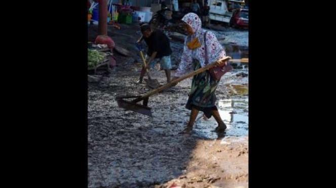 Warga membersihkan sisa-sisa lumpur akibat banjir bandang