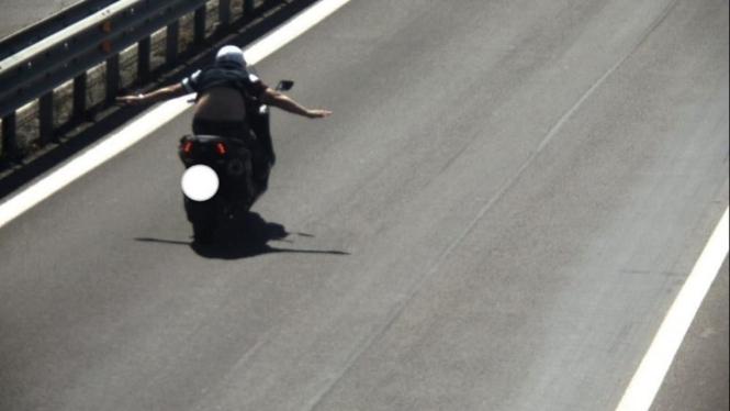 Pengendara skutik melakukan aksi nekat, melepas dua tangan saat motor melaju.