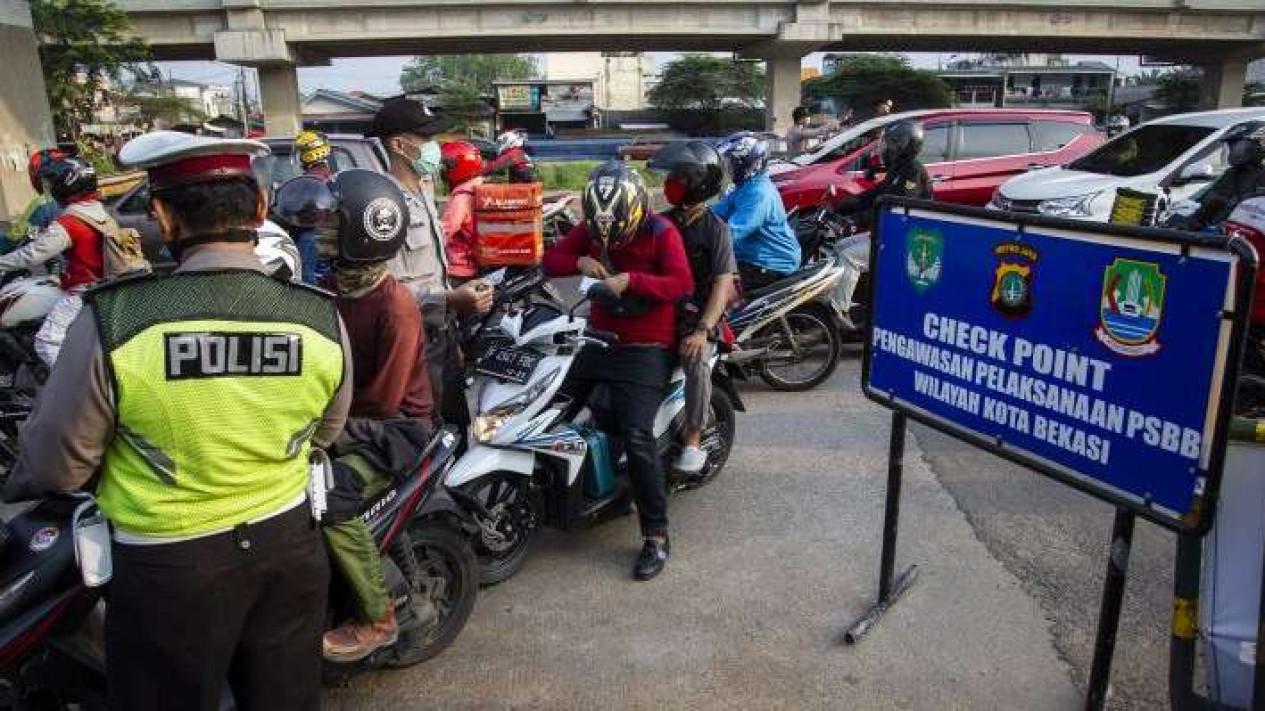 Petugas melakukan pengawasan terhadap kendaraan yang melintasi Check Point Pembatasan Sosial Berskala Besar (PSBB) di kawasan Kalimalang, Bekasi, Jawa Barat, Rabu (13/5/2020).