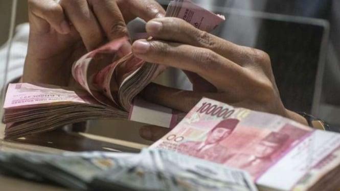 Menghitung uang kertas rupiah pecahan Rp100 ribu