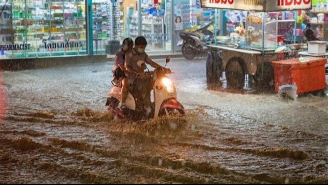 pengendara motor melewati banjir
