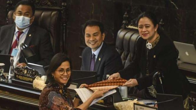 Menteri Keuangan Sri Mulyani (kedua kiri) memberikan dokumen tanggapan pemerintah kepada Ketua DPR Puan Maharani (kanan) yang disaksikan Wakil Ketua DPR Aziz Syamsuddin (kedua kanan) dan Rachmad Gobel (kiri) pada rapat paripurna DPR Kamis (18/6/2020)