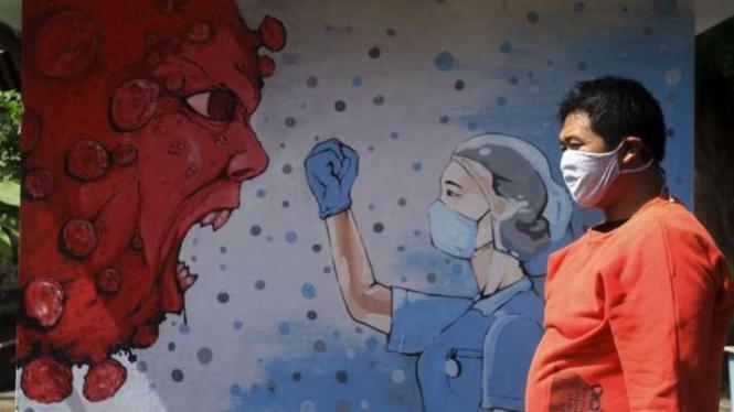 Warga melintas di dekat mural bergambar tenaga medis dan Virus Corona di Bantul (foto ilustrasi).