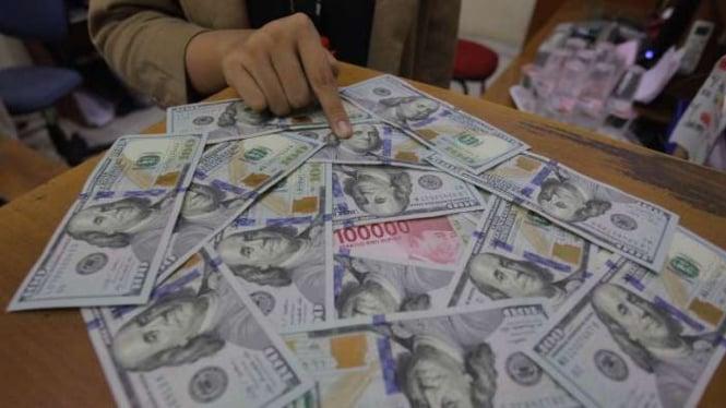 Karyawati menunjukkan mata uang rupiah dan dolar AS di salah satu gerai penukaran mata uang asing di Jakarta.