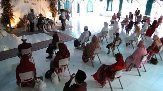 Sejumlah anggota keluarga pasangan pengantin duduk dengan jarak saat mengikuti prosesi akad nikah di Aula SD Insan Kamil, Kota Bogor, Jawa Barat, Sabtu (6/6/2020).  (Foto ilustrasi)