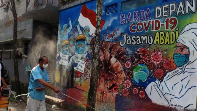 Warga menyemprotkan cairan disinfektan di depan mural