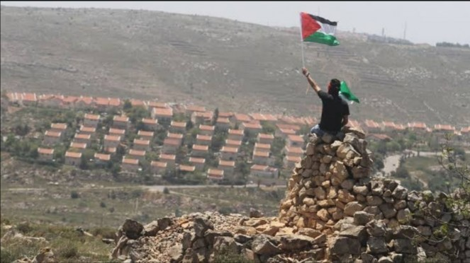 Seorang pria mengibarkan bendera Palestina di Tepi Barat.