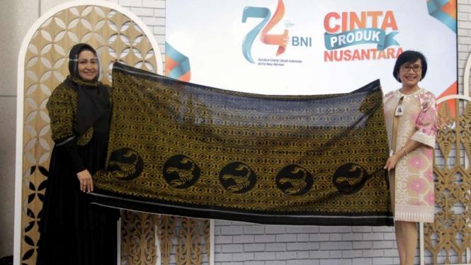 Direktur Bisnis UMKM BNI Tambok P Setyawati (Kanan) dan Pemilik Tenun Puta Dino Kayangan Anita Gathmir (Kiri) menunjukkan kain tanda apresiasi dari Kesultanan Tidore pada Show Case Cinta Produk Nusantara di Lobi Grha BNI, Jakarta, Senin (6/7) 2020.