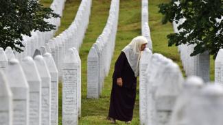 Mejra Djogaz, orang yang selamat dari insiden Srebrenica, mencium makam anaknya.-GETTY IMAGES