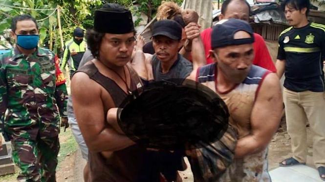 Warga mengevakuasi jasad Wawi, pria 67 tahun yang tewas di septictank. (Redaksi: Foto korban sengaja disamarkan)